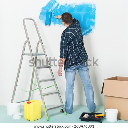 Man makes repairs at home - painting wall at room. - stock photo