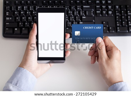 man makes the payment by credit card on holding phone