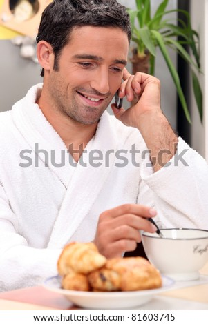 Man making a call over breakfast - stock photo