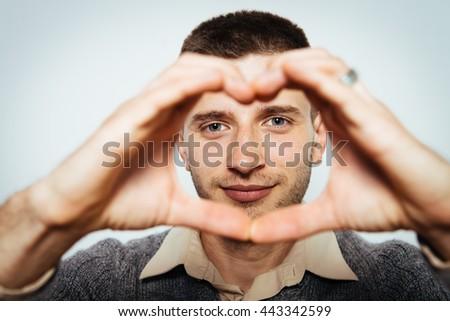 man making a hand heart frame - stock photo