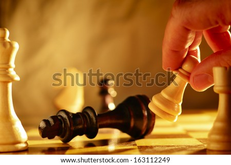 Man making a move in a game of chess knocking over a chess piece with a pawn that he is holding in his hand, close up view of the chess board - stock photo