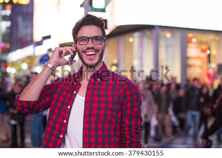 Man making a phone call on Times Square, New York, at night. - stock photo