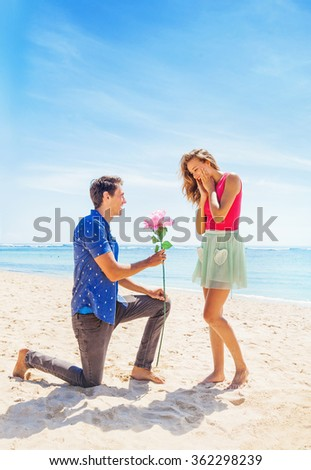 man making a proposal to a woman on a beach - stock photo