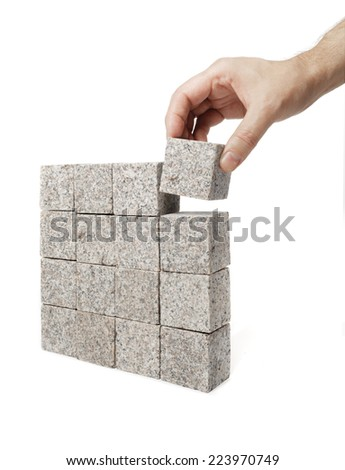 Man making a square shape of blocks made of granite rock. - stock photo