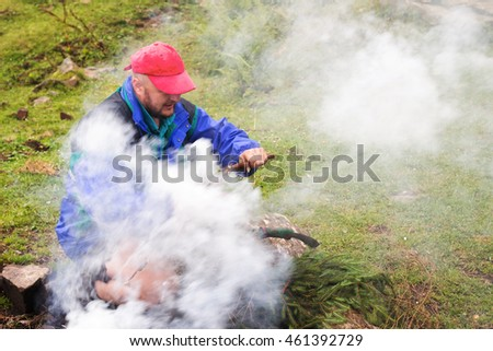 Man making campfire in Carpathian mountains, summertime journey