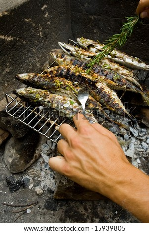 Man making grilled fishes - stock photo