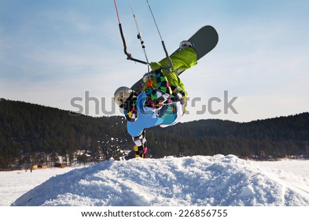 Man making hand stand on snowdrift winter snowkiting on a frozen lake