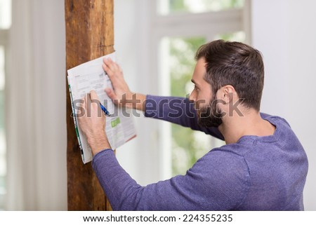 Man making notes on the classifieds section in the newspaper as he reads through the listed advertisements leaning up against a wall - stock photo