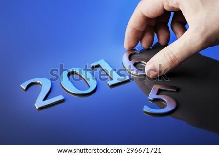 Man making number 2016 using metallic numbers. - stock photo