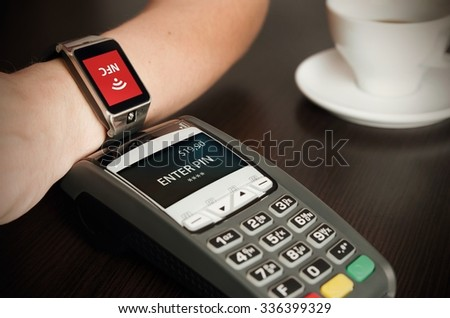 Man making payment through smartwatch via NFC contactless technology - stock photo
