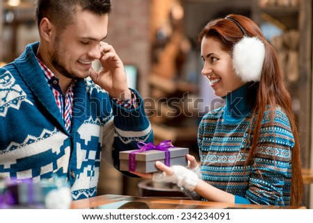 Man making proposal giving a gift box to his girlfriend dressed in blue sweaters in the cafe - stock photo