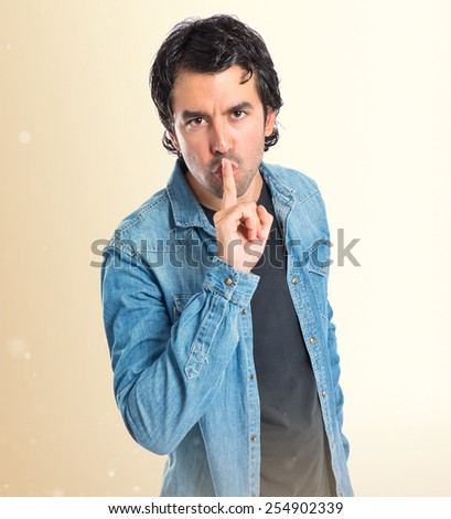 Man making silence gesture over ocher background - stock photo