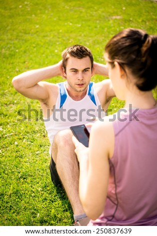 Man making sit-ups while woman is watching time of exercise on mobile phone - stock photo