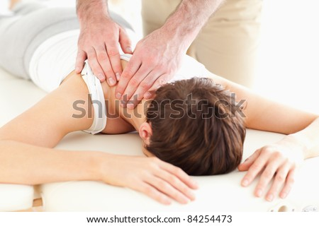 Man massaging a woman's neck in a room - stock photo