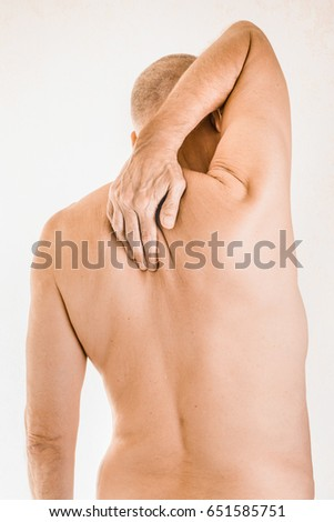 Man massaging his top back, between the shoulders, because of a thoracic vertebrae pain due to a displacement of a dorsal vertebra rubbing on a nerve