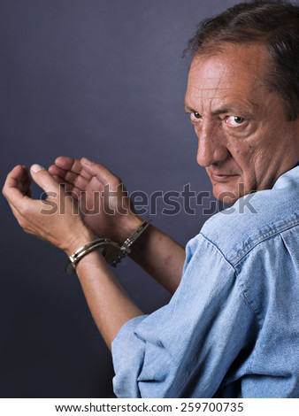Man, mature, with handcuffs - stock photo