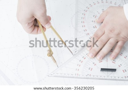 man measure by divider and triangles on map - stock photo