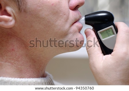 man measures the level of blood alcohol by Breathalyzer - stock photo