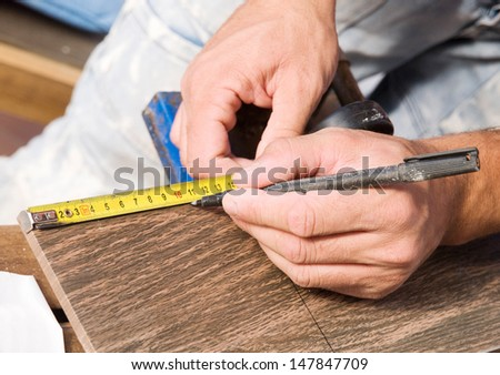 Man measuring a tile piece with a marker.The photo shows a detail of a construction job. - stock photo