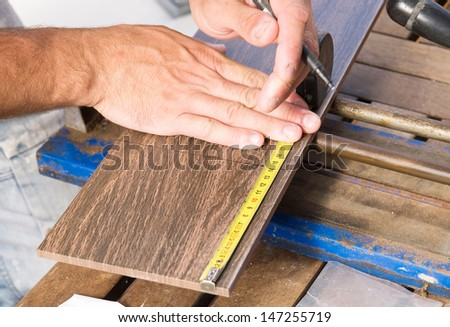 Man measuring a tile piece with a meter. - stock photo