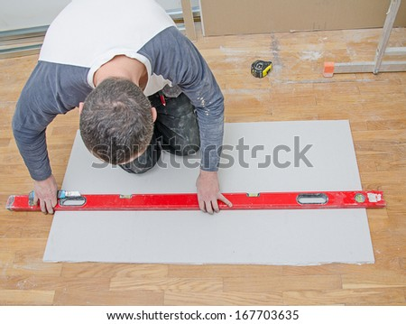 Man measuring and cutting gypsum plasterboard - stock photo