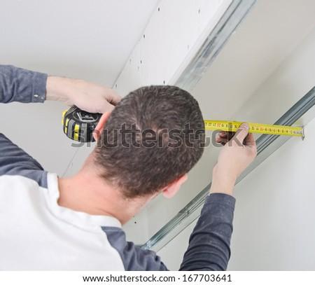 Man measuring gypsum plasterboard frame - stock photo