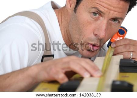 Man measuring piece wood - stock photo