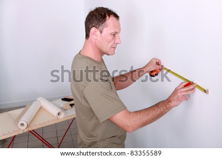 Man measuring wall - stock photo