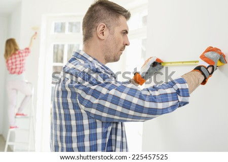 Man measuring wall with woman painting in background - stock photo