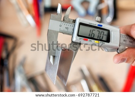 man measuting part with calipers in workshop