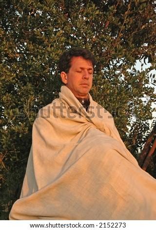 Man meditates peacefully at sunset - stock photo