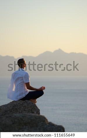 Man meditating by the sea - stock photo