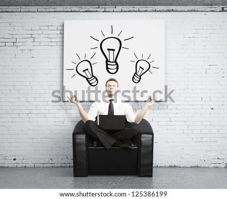 man meditating in brick room, idea concept - stock photo
