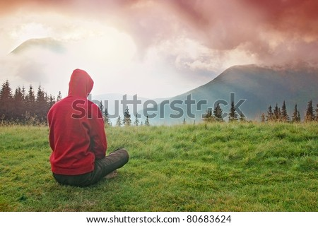 Man meditating in the mountains during the dawn - stock photo