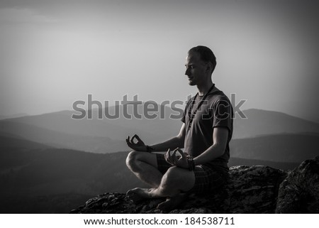 man meditating on a rock - stock photo
