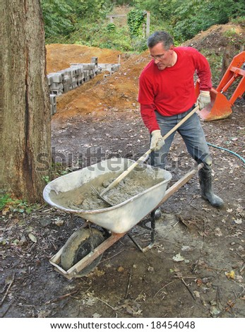 Man mixing mortar for concrete block wall - stock photo