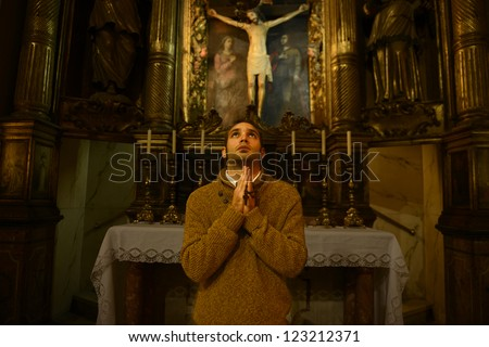 man, monk praying at the altar inside the church - stock photo