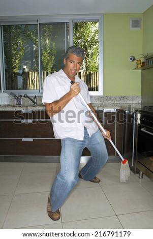 Man mopping the kitchen floor. - stock photo