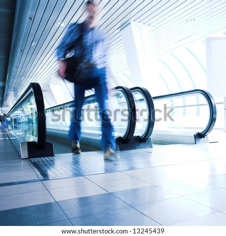 Man move in glass corridor in airport - stock photo