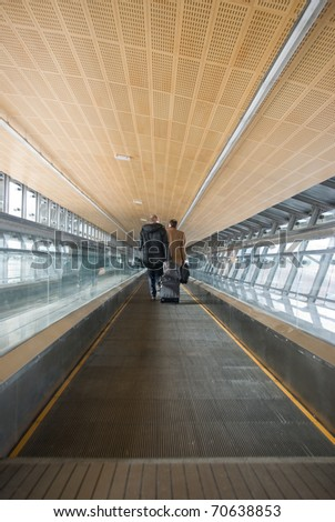 Man move in glass corridor in airport . Malaga. - stock photo