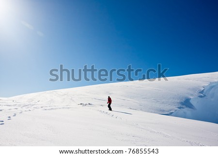 Man moves on snowboard. Glacier in background. Antarctica - stock photo