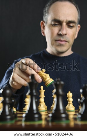 Man moving a chess piece on wooden chessboard - stock photo