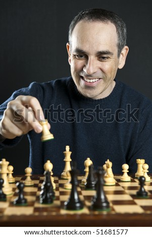 Man moving a chess piece to win the game