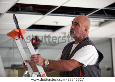 Man moving a ladder - stock photo