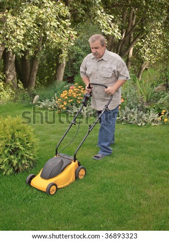 Man, mowing a grass on a lawn