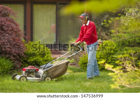 Man mowing overgrown grass lawn - stock photo