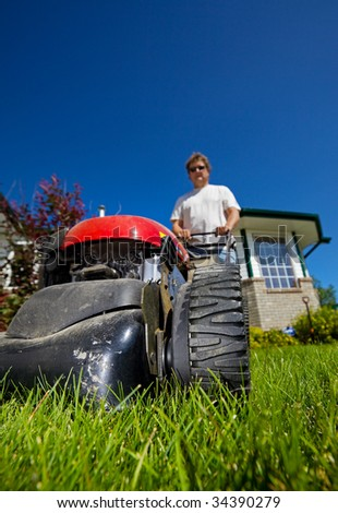 man mowing the front lawn with focus on the front - stock photo