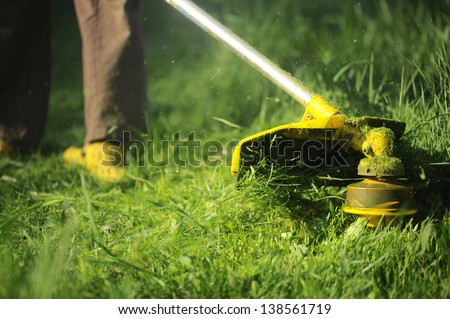 man mowing the grass, the mower close up - stock photo