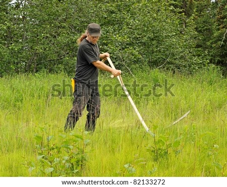 Man mowing the old fashioned way with a scythe