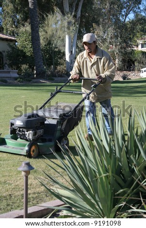 Man mowing yard of an upscale home - stock photo